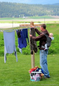 father and son taking down laundry